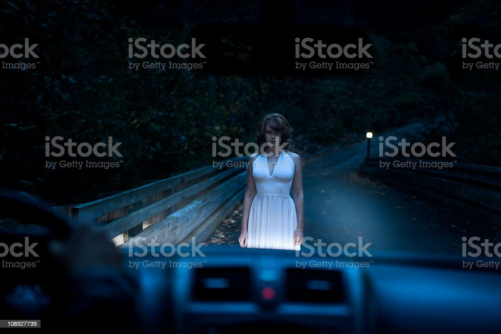 Beautiful Ghostly Woman Standing on Road in Car Headlights stock photo