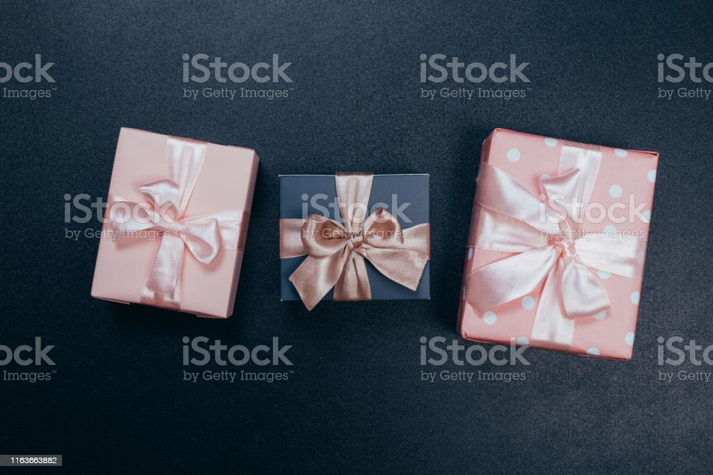 beautiful gift boxes wrapped in paper with red, gold and pink ribbon...