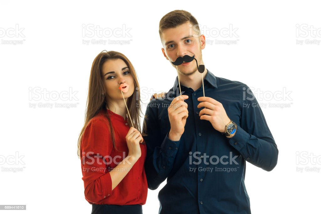 beautiful girl and a young guy hold near face paper Dummies for photo and looking at camera stock photo