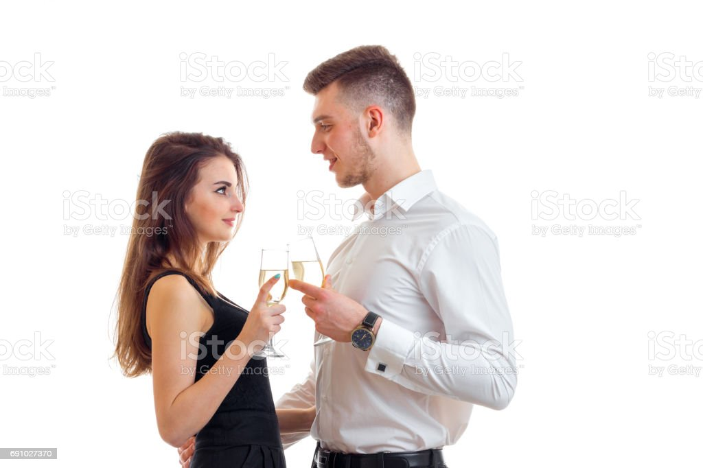 beautiful girl and charming guy stare at each other and holding wine glasses stock photo