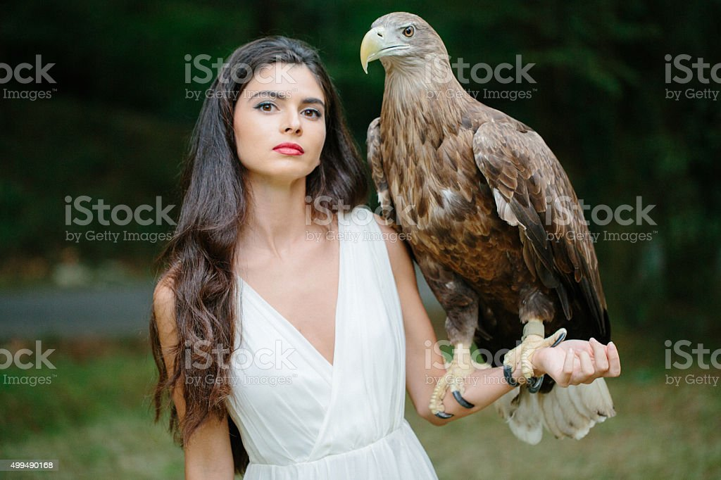 Beautiful girl and her eagle stock photo