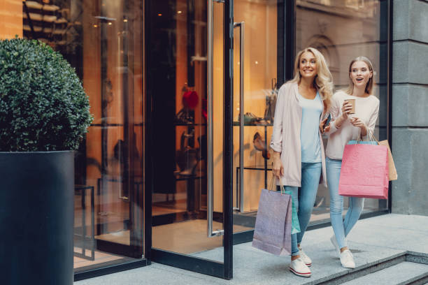 Beautiful girl and her mother standing near shoe store stock photo