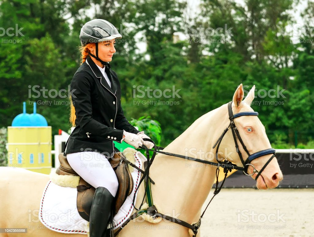 Isabelline Akhal-Teke mare with blue eyes and pretty redhead woman in...