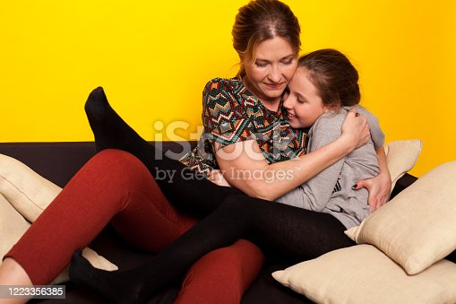 1003539592 istock photo beautiful girl and wjman lies on a black sofa in homemade clothes with pillows 1223356385