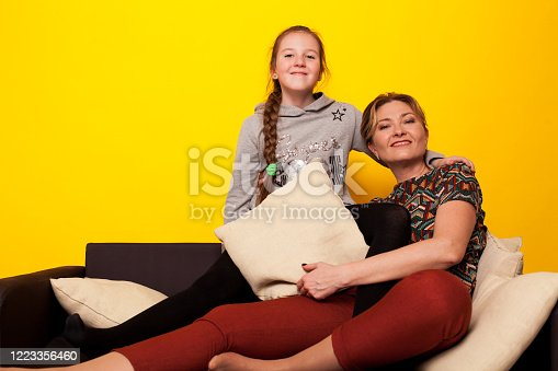 1003539592 istock photo beautiful girl and wjman lies on a black sofa in homemade clothes with pillows 1223356460