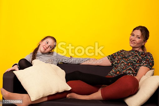 1003539592 istock photo beautiful girl and wjman lies on a black sofa in homemade clothes with pillows 1223356984