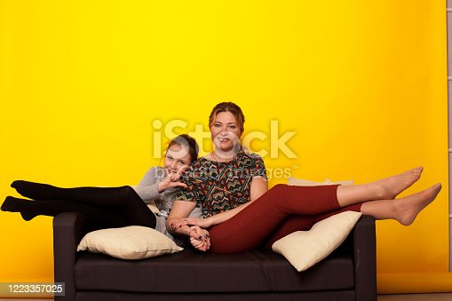 1003539592 istock photo beautiful girl and wjman lies on a black sofa in homemade clothes with pillows 1223357025