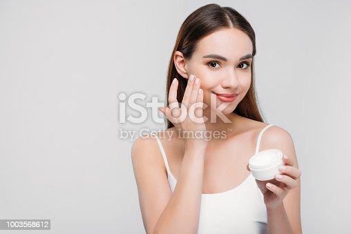 beautiful girl applying cosmetic cream on face, isolated on grey