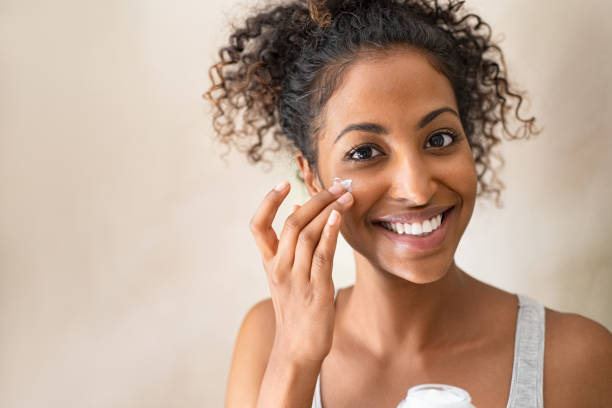 Beautiful girl applying face cream Smiling african girl with curly hair applying facial moisturizer while holding jar and looking at camera. Portrait of young black woman applying cream on her face isolated on beige background. Close up of happy attractive beauty woman caring of her skin standing on light brown wall with copy space. human skin stock pictures, royalty-free photos & images