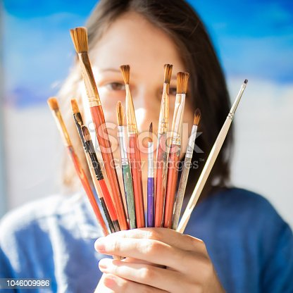 Beautiful girl artist draws a picture, holding different brushes in her hands, choosing brush for painting.
