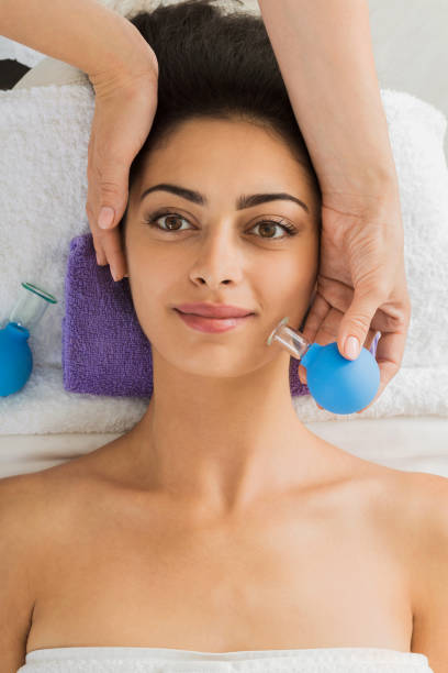 beautiful girl at cupping massage in spa wellness center - cupping therapy stock photos and pictures