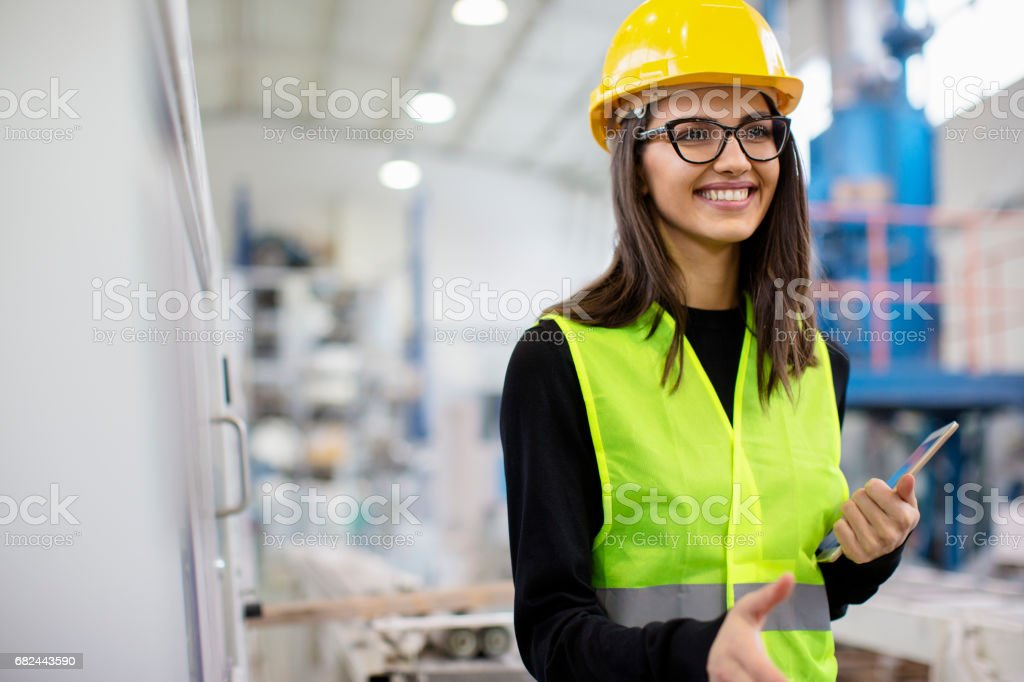 Beautiful girl at factory in a vest and helmet smiling going for a handshake royalty-free stock photo