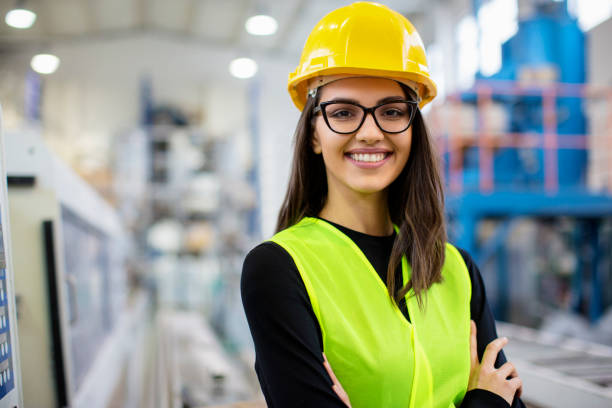 Beautiful girl at factory in a vest and helmet smiling. stock photo