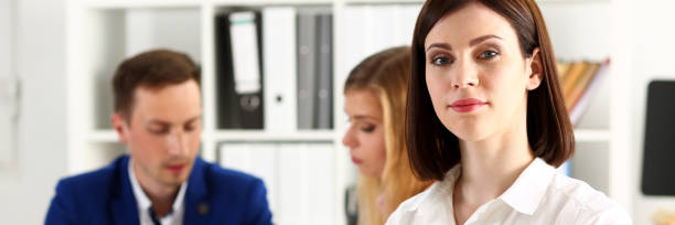 Beautiful girl at workplace look in camera Beautiful girl at workplace look in camera with colleagues group in background hands crossed. White collar worker at workspace, job offer, modern lifestyle, client visit, profession train concept letterbox format stock pictures, royalty-free photos & images