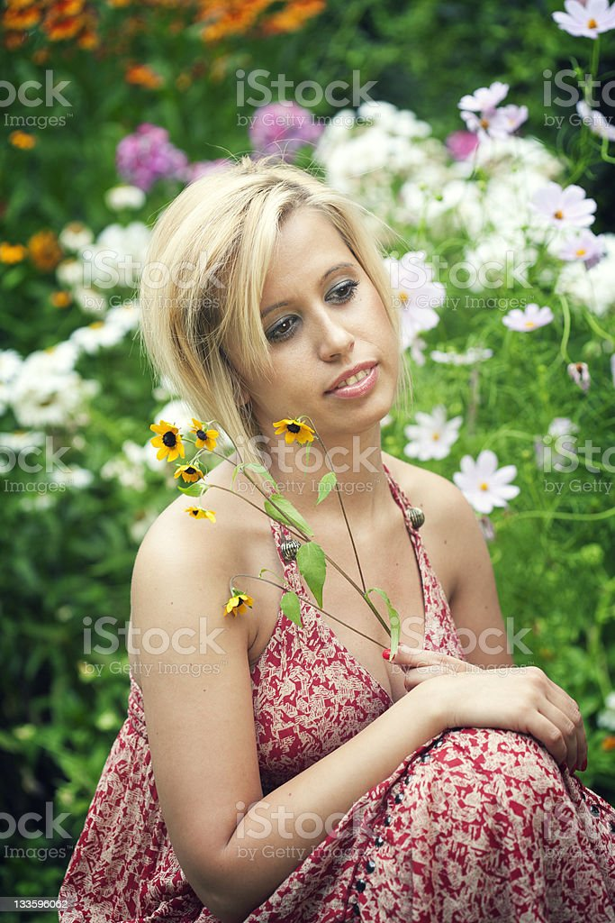 Beautiful girl between flowers stock photo