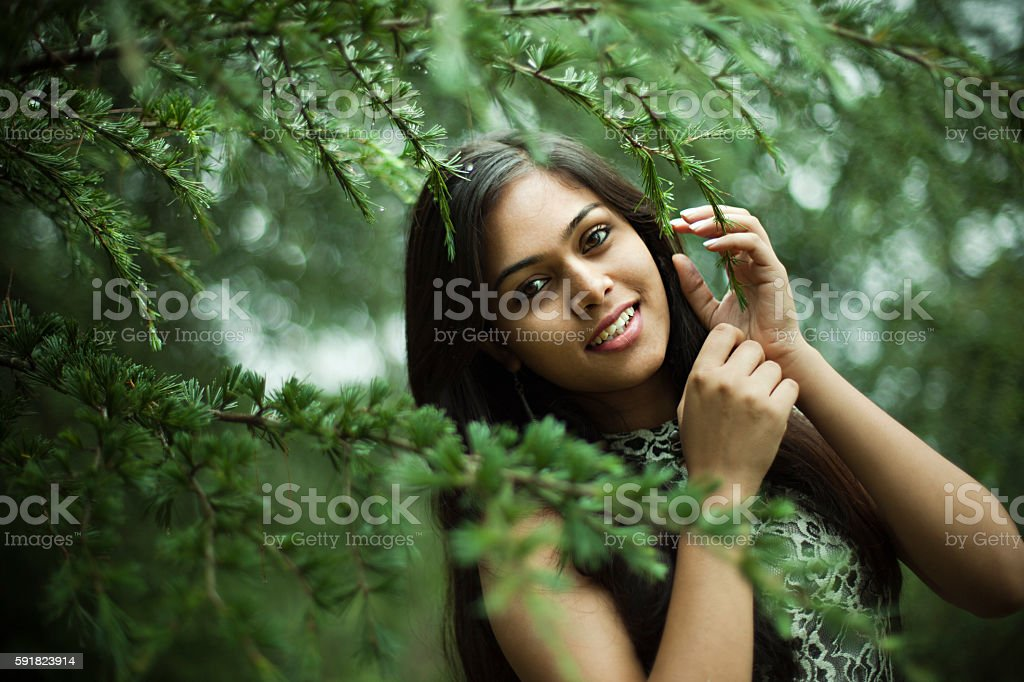 Beautiful girl between nature full of branches of pine tree. stock photo