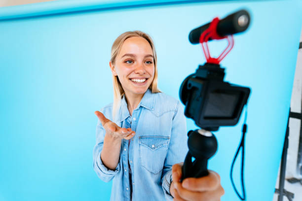 Beautiful girl blogger relieves itself at camera isolated blue background stock photo