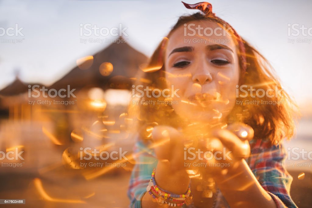 Beautiful  girl blowing glitter in the sun at the beach stock photo