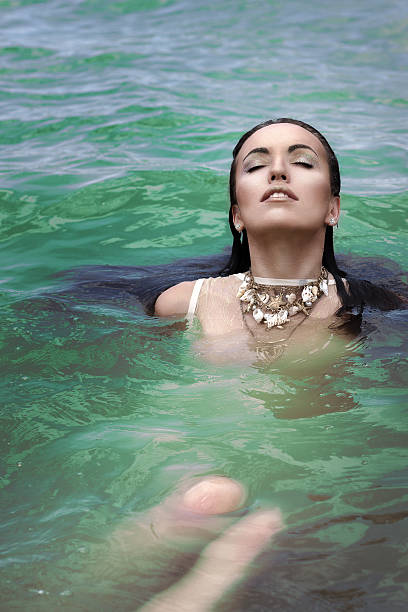 Beautiful girl brunette in green lake swimming in clothes stock photo