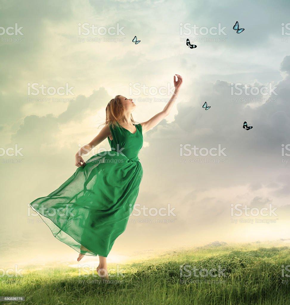 Beautiful girl catching butterflies on a mountain stock photo
