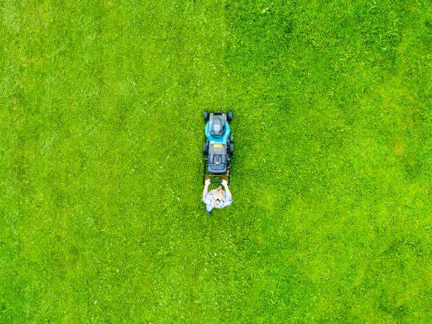 Schöne Mädchen schneidet den Rasen. Rasenmähen. Luftbild schöne Frau Rasenmäher auf grünem Gras. Mähgrasausrüstung. Mähen Gärtner Pflege Arbeitswerkzeug. Nahansicht. Luftrasenmähen – Foto