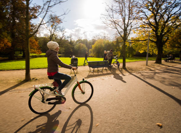 Beautiful girl cycling outside at sunny autumn day. stock photo