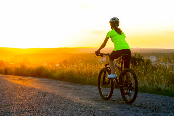Beautiful girl cyclist riding a bike on the road towards the sunset. Nature and recreation. Hobbies and sports stock photo