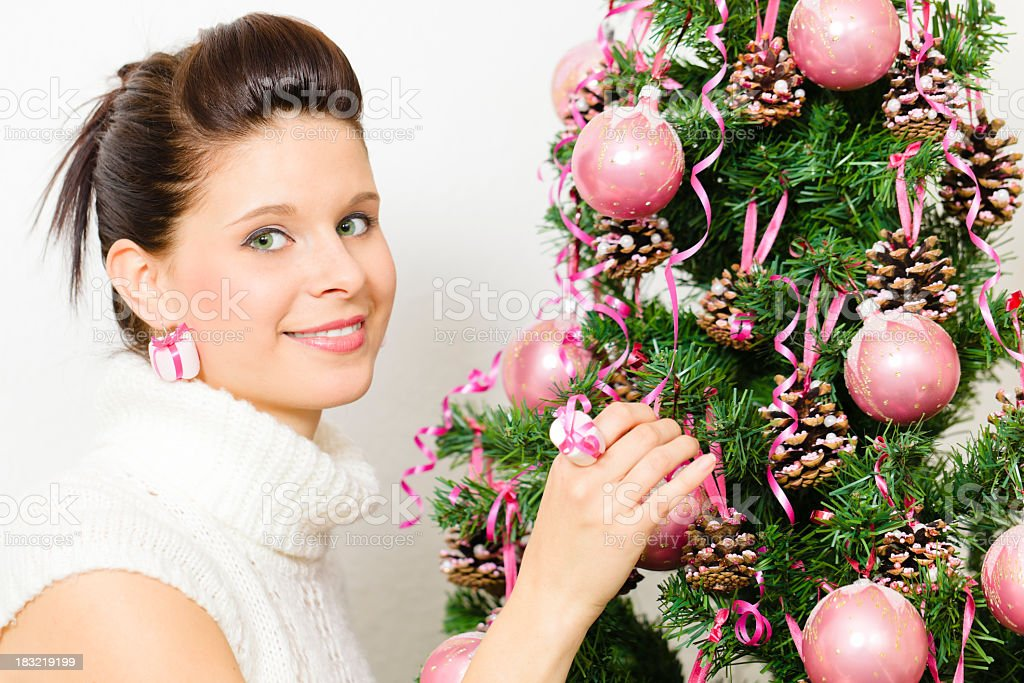 Beautiful girl decorating a Christmas tree royalty-free stock photo