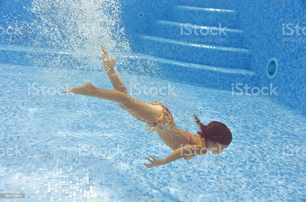 Beautiful girl dives and swims underwater in pool royalty-free stock photo