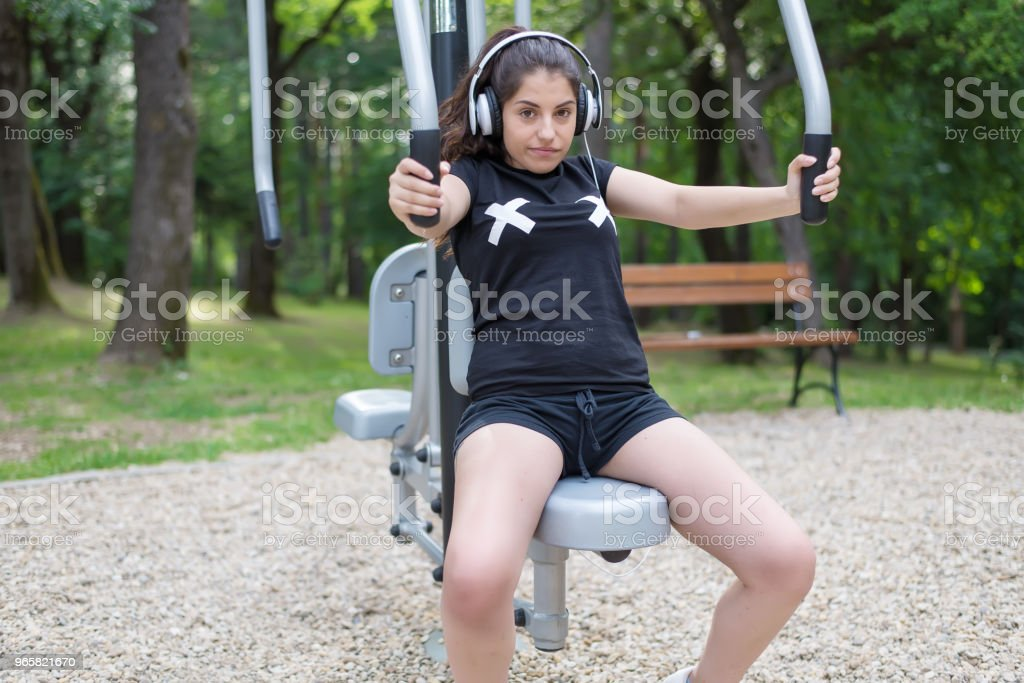 Een mooi meisje doen oefeningen buiten en luisteren naar muziek. - Royalty-free Activiteit - Bewegen Stockfoto