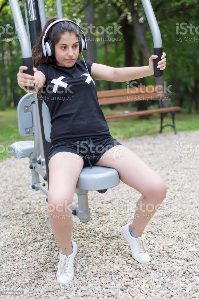 A beautiful girl doing exercises outside and listening to music. - Royalty-free Adult Stock Photo