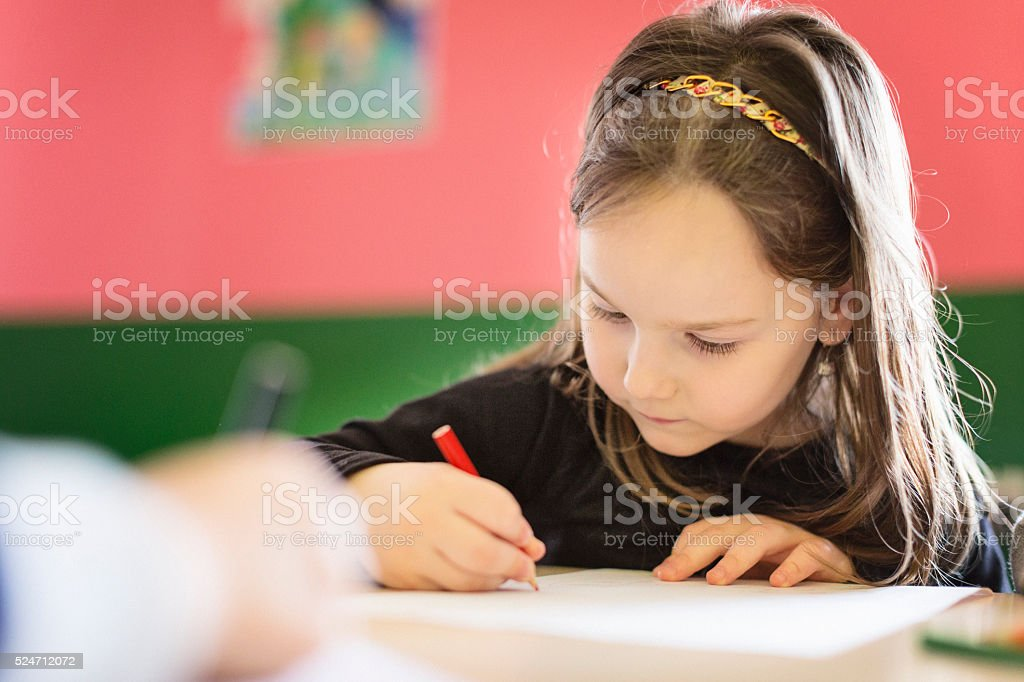 Beautiful girl drawing in the classroom stock photo