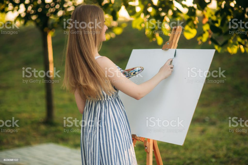 Beautiful girl draws a picture in the park using a palette with paints and a spatula. Easel and canvas with a picture. Summer is a sunny day, sunset stock photo