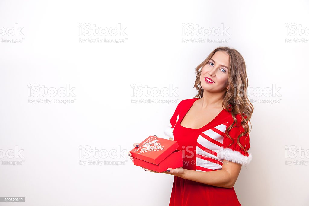Beautiful girl dressed as Santa Claus opens a gift zbiór zdjęć royalty-free