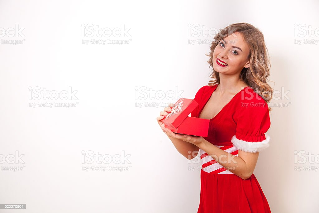 Beautiful girl dressed as Santa Claus opens a gift foto de stock royalty-free