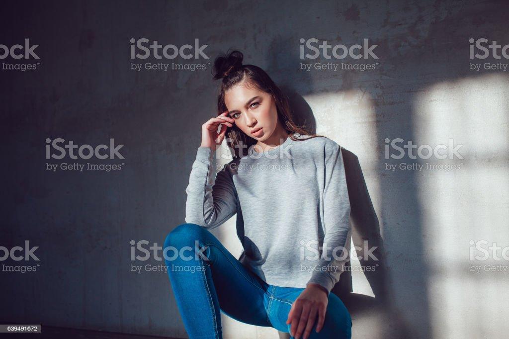 Beautiful girl dressed in blank sweatshirt sitting on a gray stock photo