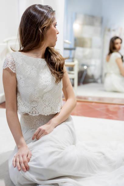 schönes mädchen, das in brautkleid gekleidet ist, während sie auf dem boden in der nähe des spiegels sitzen - hochzeitskleid marken stock-fotos und bilder