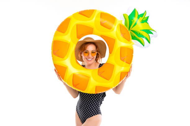 beautiful girl dressed in retro swimsuit and a straw hat holds a swimming circle in the shape of pineapple on a white background stock photo