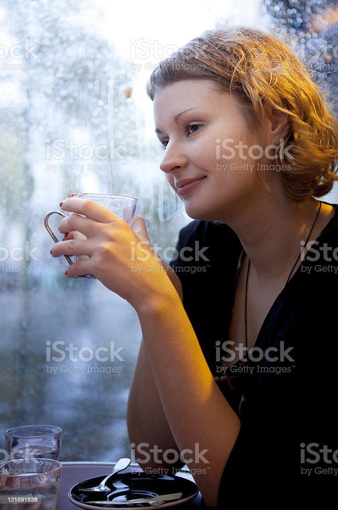 Beautiful girl drinking cappuccino in a Parisian cafe at rain royalty-free stock photo
