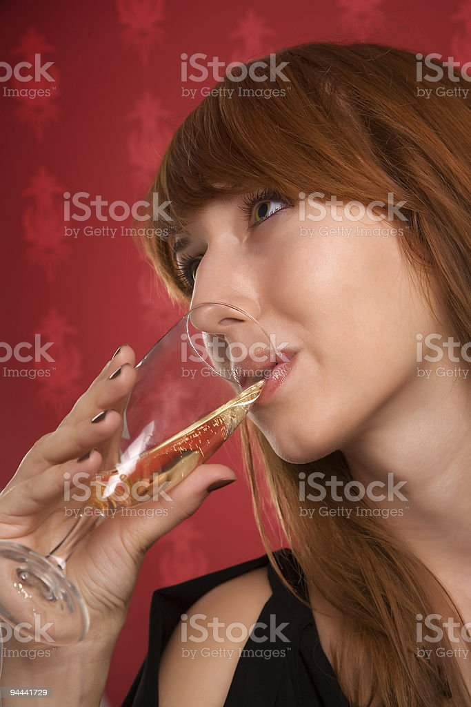 Beautiful girl drinking champagne on wallpaper background royalty-free stock photo