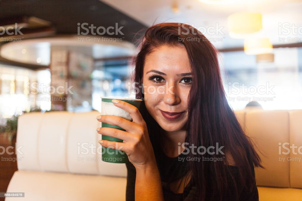 Beautiful girl drinking coffee at the coffee shop stock photo