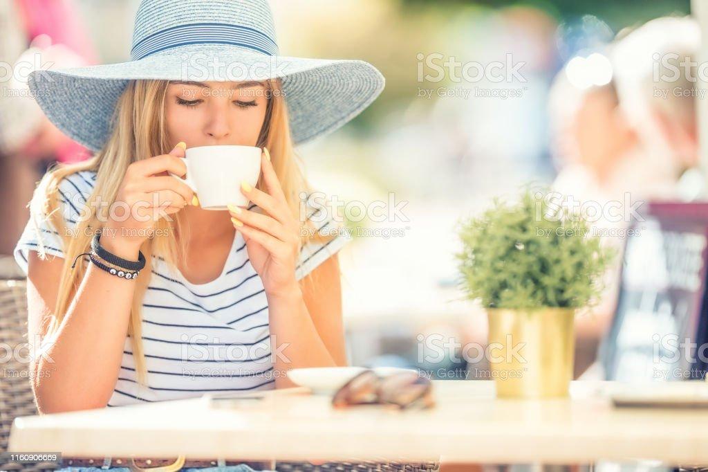 Beautiful girl drinking coffee in a cafe terrace. Summer portrait...