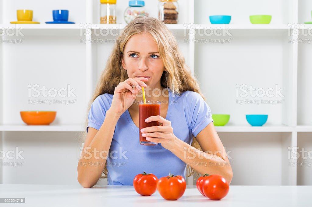 Beautiful girl drinking tomato juice stock photo