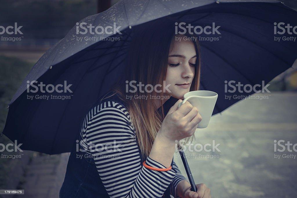 beautiful girl during a rain under umbrella drinks hot coffee royalty-free stock photo