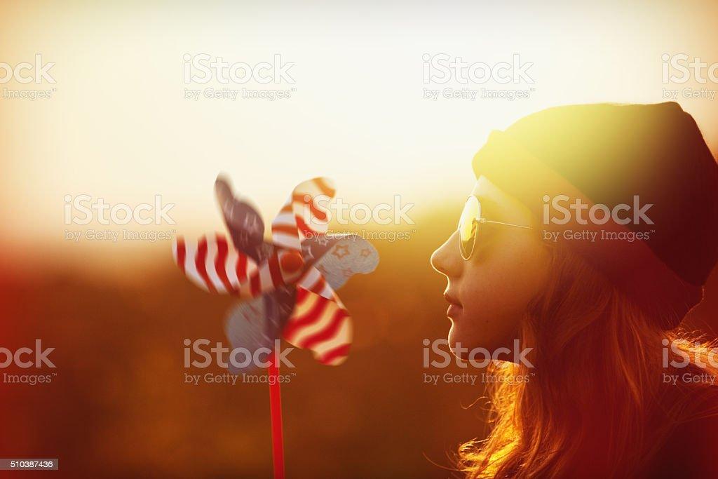 Beautiful Girl During Sunset With Pinwheel stock photo