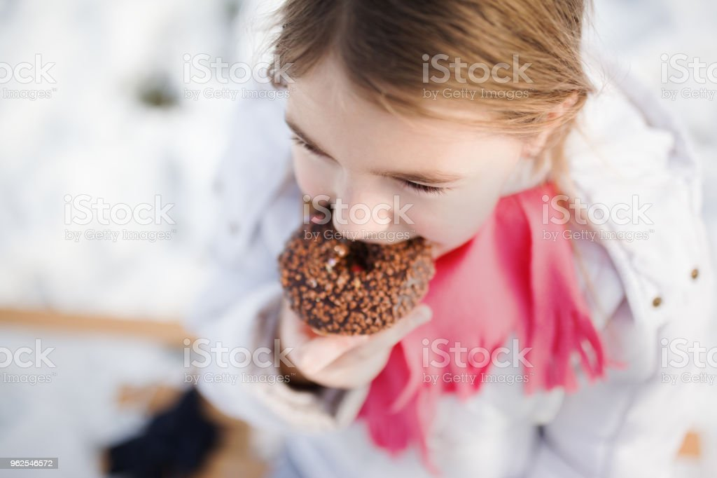 Beautiful girl eating a donuts while snowing stock photo