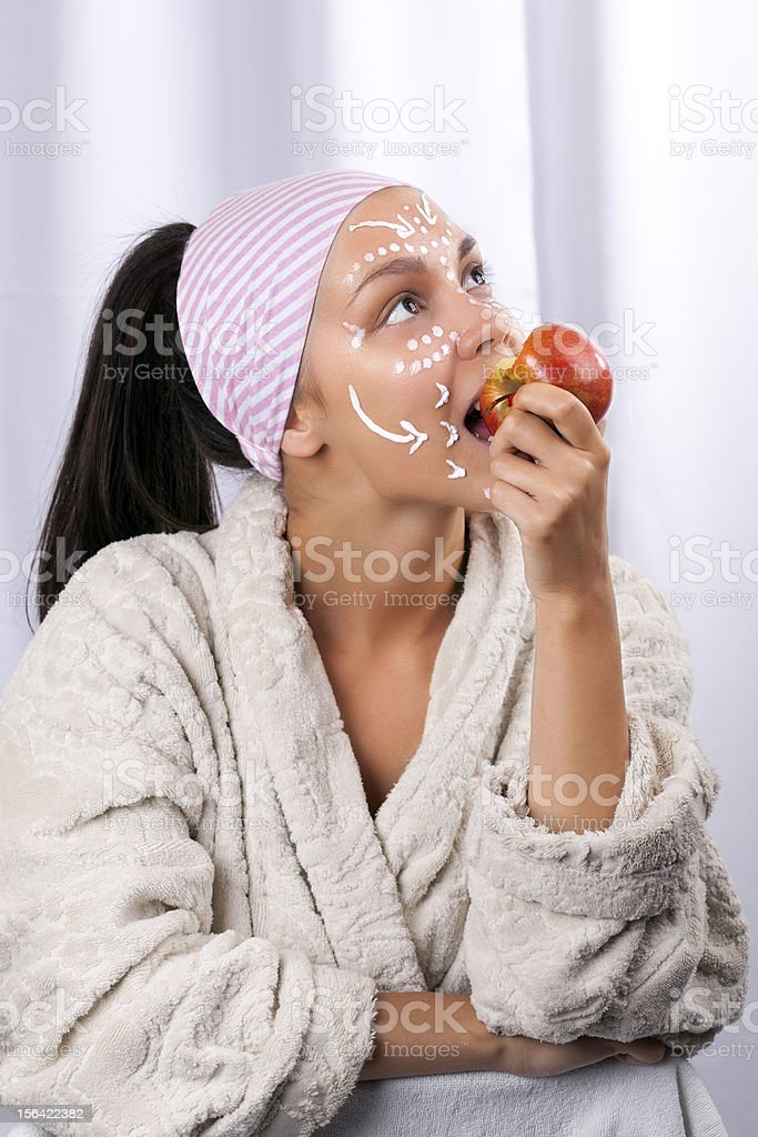 Beautiful girl eating apple in the spa center royalty-free stock photo
