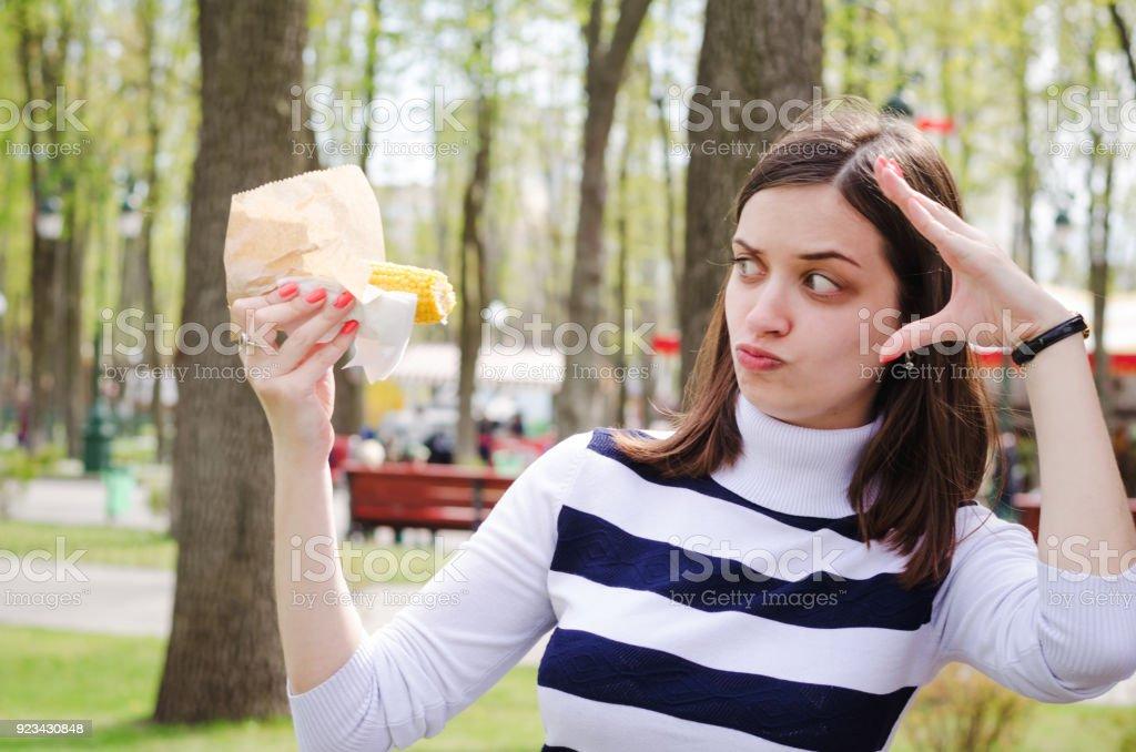 Belle fille manger du maïs délicieux dans un parc un jour de printemps ensoleillé, s'amuser et montrant le théâtre - Photo