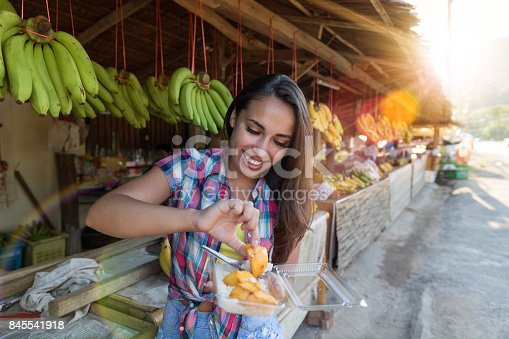 istock Beautiful Girl Eating Exotic Fruits On Traditional Street Market Happy Smiling Attractive Female Tourist In Asian Bazaar 845541918
