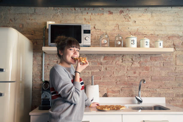 Beautiful girl eating pizza in a modern kitchen stock photo